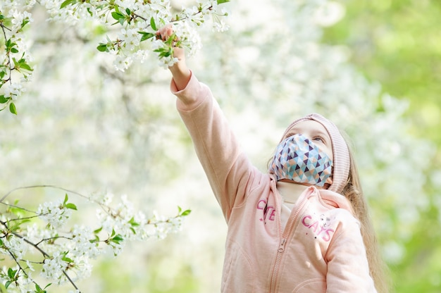 Una bambina in una mascherina medica esamina un fiore dell'albero.