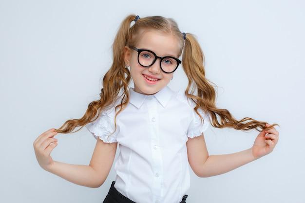 Una bambina in uniforme scolastica e bicchieri su uno sfondo bianco