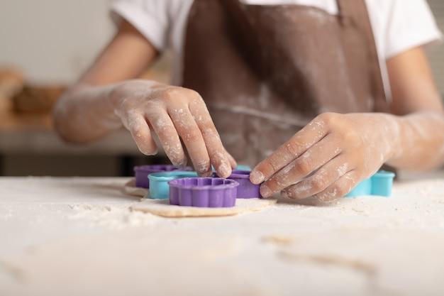 Una bambina indossa un grembiule marrone usando uno stampo viola per tagliare l'impasto