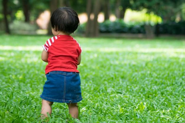 Una bambina inizia a camminare per prima e in piedi sull'erba verde