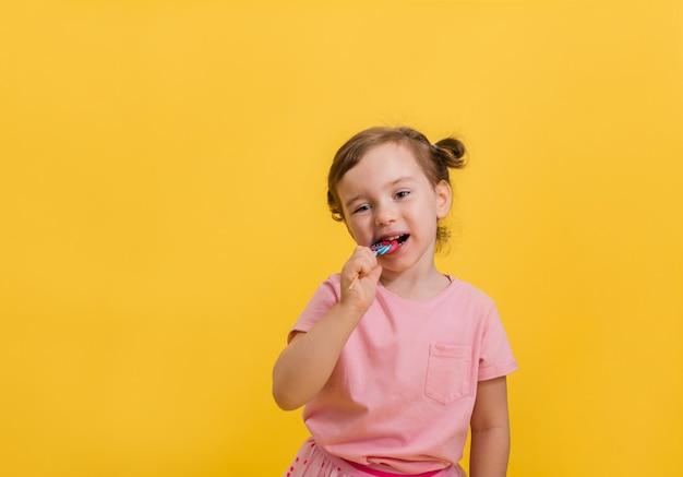 Una bambina mangia una lecca-lecca su un bastone su un giallo isolato