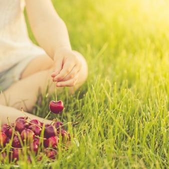 Una bambina seduta su un prato verde prende una bacca matura da un piatto di ciliegie