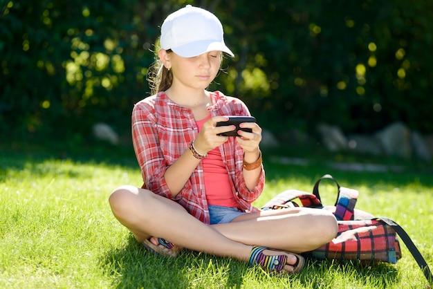 Una bambina seduta sull'erba a giocare con un telefono