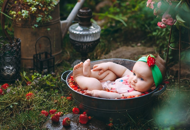 Una bambina si bagna in un bacino con fragole in giardino.