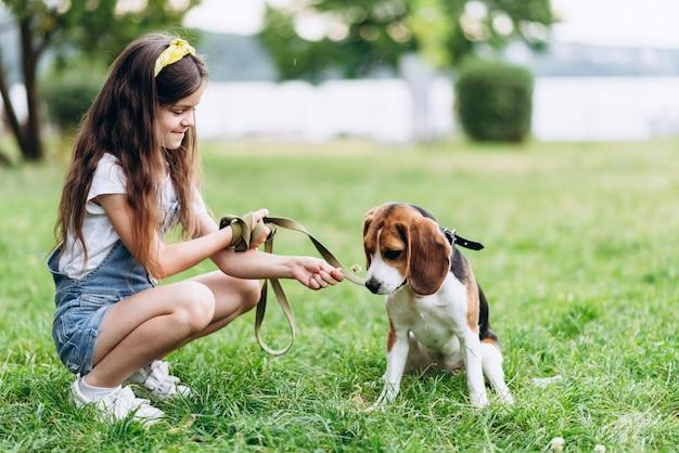 Una bambina si siede con un cane e le dà l'odore di un fiore.