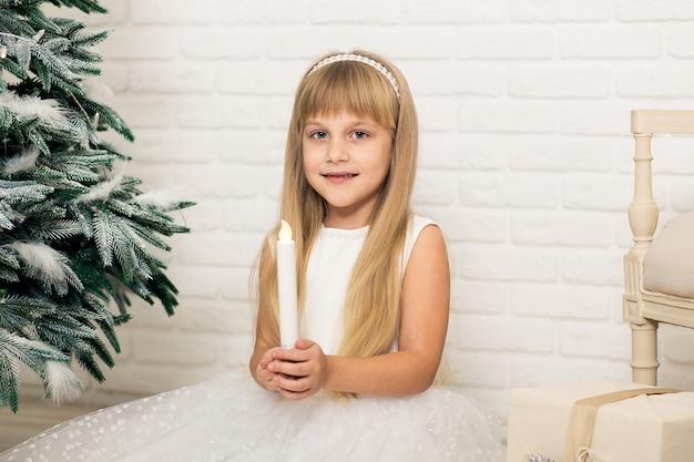Una bambina si siede e tiene una candela in mano in una stanza vicino all'albero di natale.