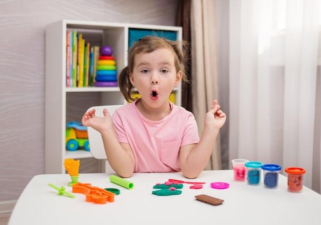 Una bambina sorpresa sta giocando a giocare a un tavolo nella stanza dei bambini