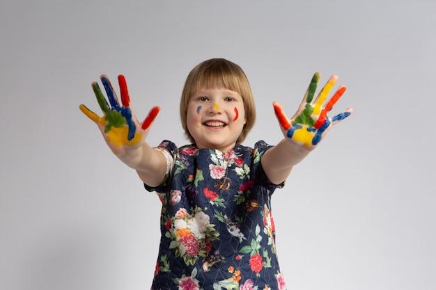 Una bambina sorridente tende le mani macchiate di vernice