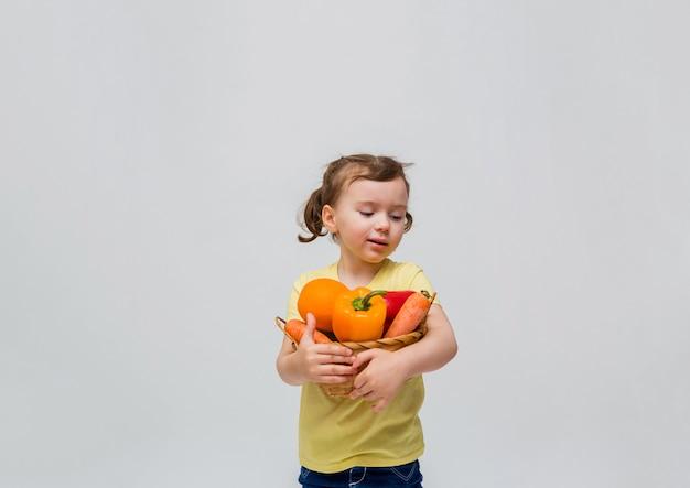 Una bambina tiene un cesto di frutta e verdura su uno spazio bianco. una ragazza carina con le trecce distoglie lo sguardo da frutta e verdura. copia spazio.