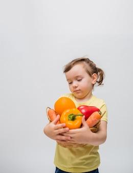 Una bambina tiene un cesto di frutta e verdura su uno spazio bianco. una ragazza carina con le trecce guarda frutta e verdura. copia spazio.