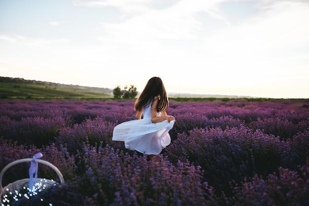 Una bambina vestita in abito bianco nel campo di lavanda