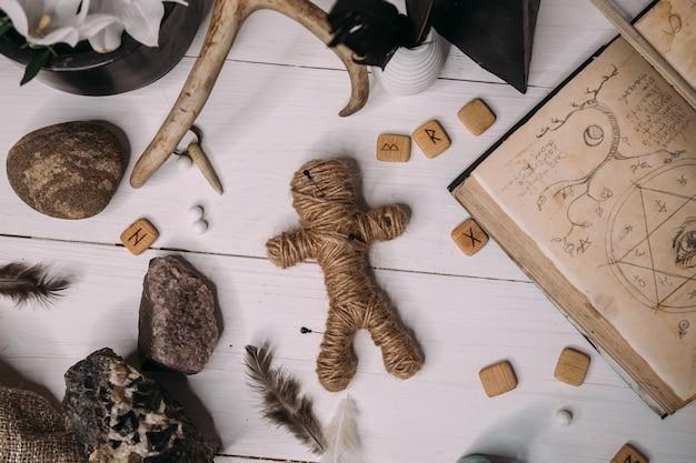 Una bambola voodoo fatta di corda giace con un vecchio libro grimorio, circondata da oggetti rituali magici, distesi