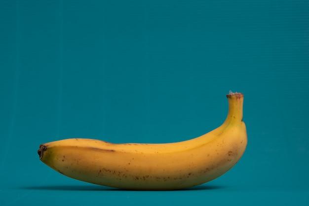 Una banana su uno sfondo blu chiaro.