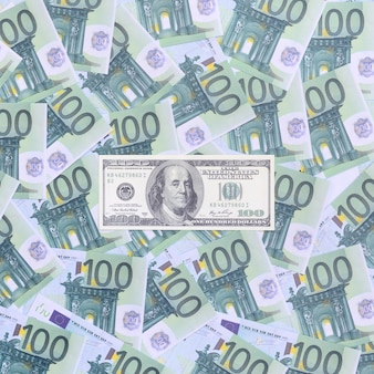 Una banconota da 100 dollari si trova su un insieme di denominazioni monetarie verdi di 100 euro.