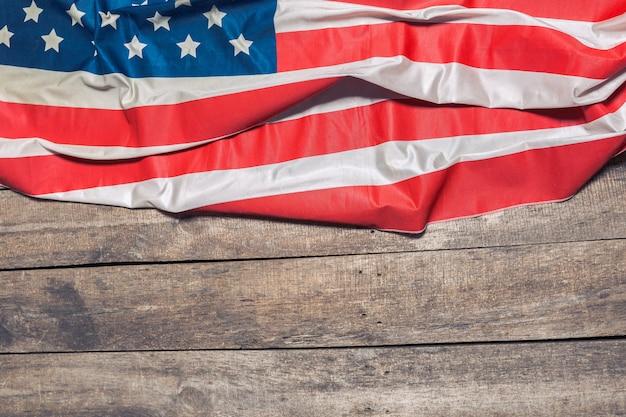 Una bandiera americana che giace su un legno rustico invecchiato e stagionato