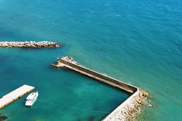 Una barca bianca solitaria ormeggiata al mare in giornata di sole. molo con accesso al mare blu.
