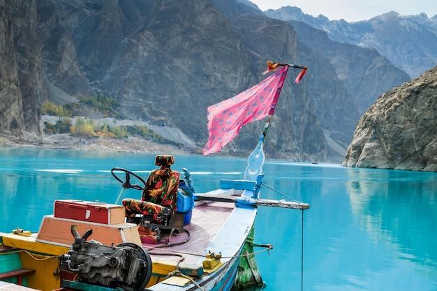 Una barca colorata nel lago attabad. valle della hunza, gilgit baltistan, pakistan.