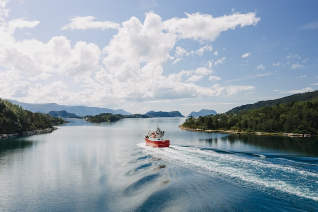 Una barca sul corpo d'acqua circondata da alberi sotto un cielo blu chiaro con nuvole bianche