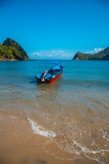 Una barca sulla spiaggia di puerto caribe a punta de sal nel mar dei caraibi, tela. honduras
