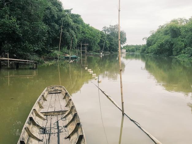 Una barca tradizionale si trova nel canale locale circondato da foreste naturali