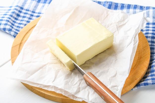 Una barra di burro su una tavola di legno con un coltello, su un tavolo bianco. ingredienti per cucinare