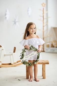 Una bella bambina che si siede su uno sgabello di legno in un bel vestito nella stanza bianca