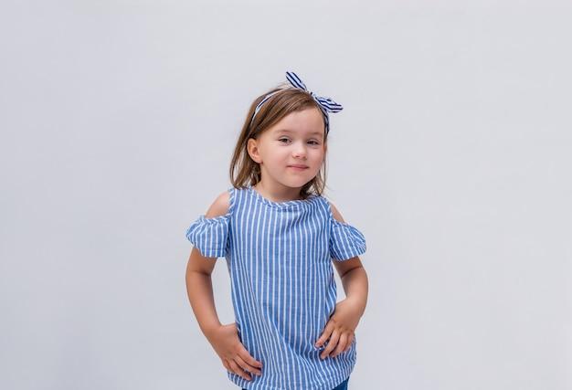 Una bella bambina in una camicetta a righe e fascia su un bianco isolato
