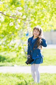 Una bella bambina tiene in mano una macchina fotografica.