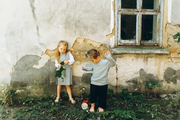 Una bella coppia di bambini in abiti grigi sta giocando contro lo sfondo del muro