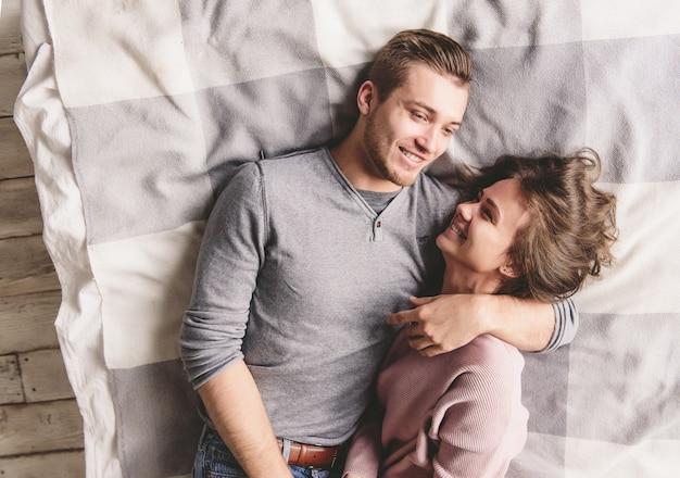 Una bella coppia di innamorati si diletta nel letto insieme. stanno abbracciando e sorridendo