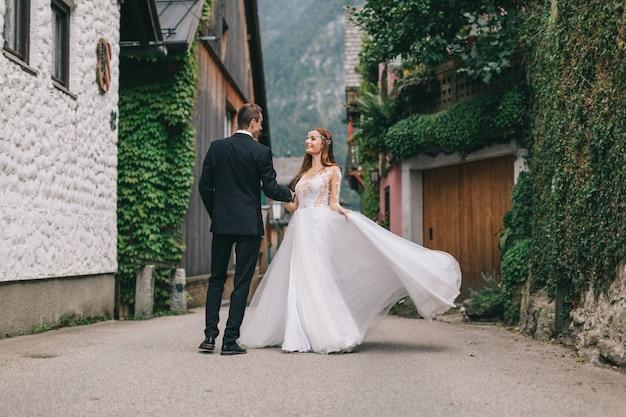 Una bella coppia di sposi cammina in una fata cittadina austriaca, hallstatt.