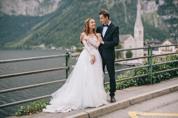 Una bella coppia di sposi cammina su una vecchia cattedrale di sfondo in una città austriaca fata