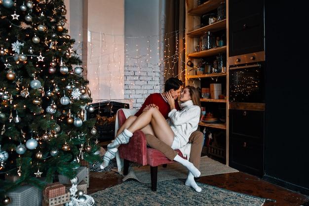 Una bella coppia innamorata abbraccia in cucina, decorata per capodanno o natale.