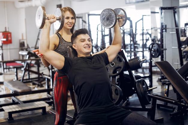 Una bella coppia sportiva è impegnata in una palestra
