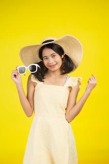 Una bella donna allegra che indossa un grande cappello con gli occhiali bianchi su un giallo.