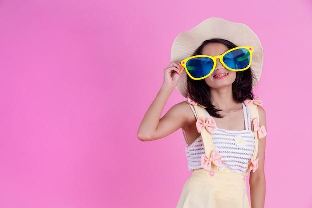 Una bella donna asiatica che indossa un cappello e grandi occhiali con una rosa.