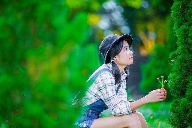 Una bella donna asiatica che indossa un cappello per rilassarsi e godersi il verde del giardino come sfondo.