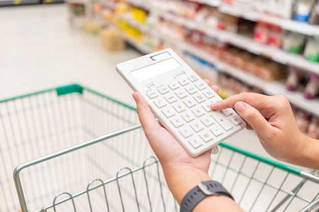 Una bella donna asiatica in possesso di un calcolatore per calcolare il costo e la riduzione dei prezzi