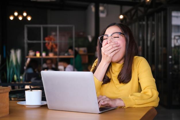 Una bella donna asiatica in un abito giallo. dolore alla spalla e occhi chiusi. usa un laptop al bar.
