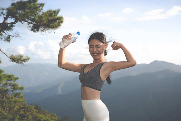 Una bella donna asiatica meditando ed esercitandosi sulla cima della montagna.