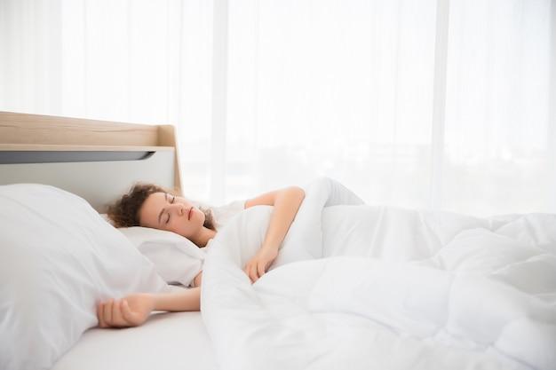 Una bella donna bianca con i capelli ricci dorme, riposa e dorme su un letto in una camera da letto bianca.