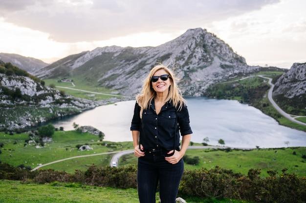 Una bella donna bionda caucasica che indossa abiti casual in un paesaggio montuoso con lago