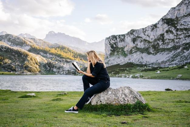 Una bella donna bionda caucasica legge un libro in un paesaggio montuoso con un lago