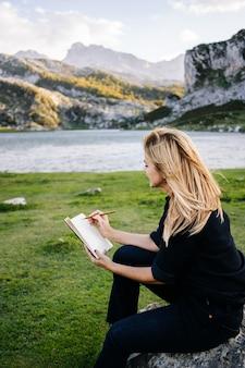 Una bella donna bionda caucasica scrive e disegna su un blocco note in un paesaggio montano con lago