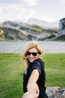 Una bella donna bionda caucasica tiene la mano di un uomo in un paesaggio montuoso con lago
