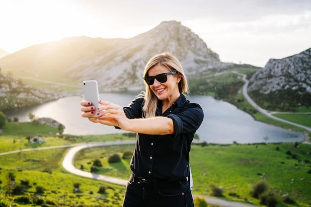 Una bella donna bionda caucasica utilizza il telefono in un paesaggio montuoso con lago