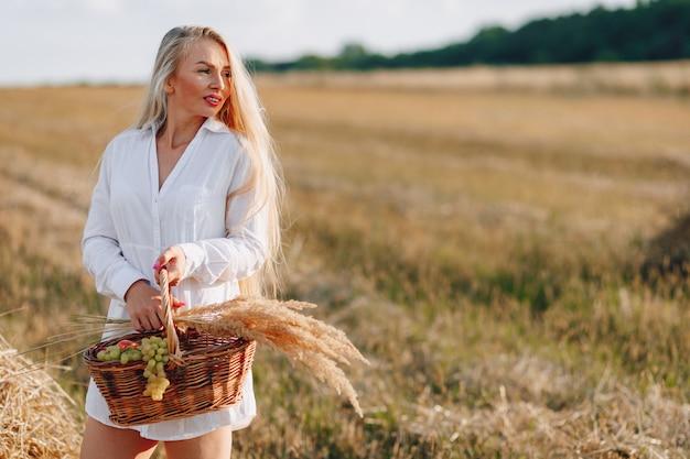 Una bella donna bionda con i capelli lunghi in un campo al tramonto porta un cesto di frutta e un mazzo di paglia. estate, agricoltura, natura e aria fresca in campagna.