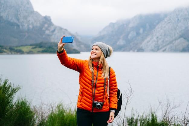 Una bella donna bionda turistica, con un cappello di lana, uno zaino e un cappotto arancione, scatta una foto di selfie con il cellulare in un paesaggio con lago e montagne