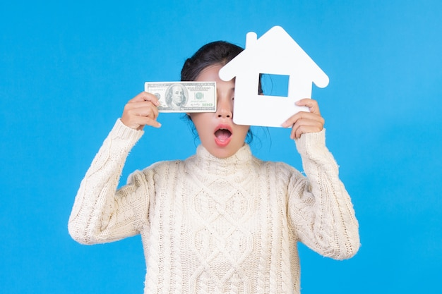 Una bella donna che indossa un nuovo tappeto bianco a maniche lunghe che detiene il simbolo della casa e banconote da un dollaro su un blu. trading.