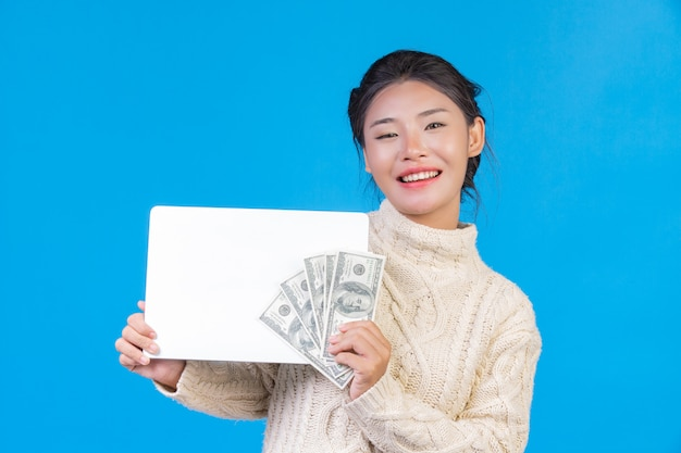 Una bella donna che indossa un nuovo tappeto bianco a maniche lunghe con un cartello bianco e una banconota in dollari su un blu. trading.
